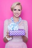 Bella donna bionda con il vestito crema che dà regalo variopinto immagine stock