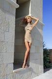 Bella donna bionda con le gambe lunghe nel vestito a cristallo carnoso Fotografia Stock