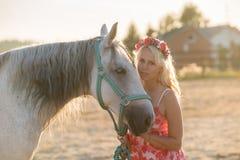 Bella donna bionda con un cavallo Fotografie Stock