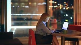 Bella donna bionda di affari che lavora fuori orario alla notte in ufficio esecutivo Le luci della città sono visibili nel fondo archivi video