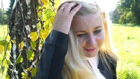 Bella donna bionda felice sorridere del parco e nel movimento lento commovente del fondo di autunno dei capelli stock footage