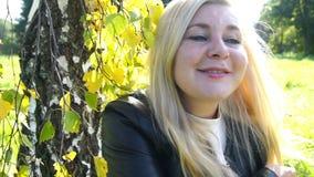 Bella donna bionda felice sorridere del parco e nel movimento lento commovente del fondo di autunno dei capelli archivi video