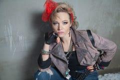 Bella donna bionda nello stile della roccia che posa sulla via Fotografie Stock Libere da Diritti