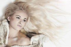 Bella donna bionda in pelliccia del visone sul pavimento. capelli lunghi immagini stock libere da diritti