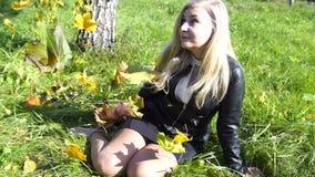 Bella donna bionda pensierosa nel fondo di silenzio di giallo di umore di autunno di ispirazione di tatto del parco video d archivio