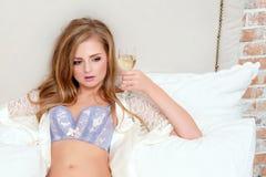 Bella donna bionda sensuale in biancheria nella sua camera da letto che tiene un vetro di vino bianco Fotografia Stock