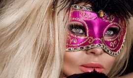 Bella donna bionda sensuale con la maschera di carnevale, stante su un fondo dei palloni neri Fotografie Stock