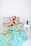 Bella donna bionda sensuale in vestito lungo splendido che tiene vetro di vino bianco con la bottiglia che sta sulla tavola Fotografia Stock Libera da Diritti