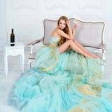 Bella donna bionda sensuale in vestito lungo splendido che tiene vetro di vino bianco con la bottiglia che sta sulla tavola Fotografia Stock