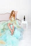 Bella donna bionda sensuale in vestito lungo splendido che tiene vetro di vino bianco con la bottiglia che sta sulla tavola Immagini Stock