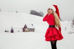 Bella donna bionda sexy che porta un vestito rosso e un cappello del ` s di Santa in montagne ed in neve Fotografie Stock