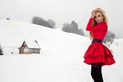 Bella donna bionda sexy che porta un vestito rosso e un cappello del ` s di Santa in montagne ed in neve Immagini Stock