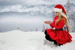 Bella donna bionda sexy che porta un vestito rosso e un cappello del ` s di Santa in montagne ed in neve Fotografie Stock Libere da Diritti