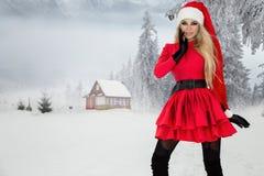 Bella donna bionda sexy che porta un vestito rosso e un cappello del ` s di Santa in montagne ed in neve Immagini Stock Libere da Diritti