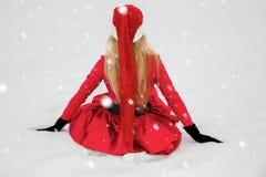 Bella donna bionda sexy che porta un vestito rosso e un cappello del ` s di Santa in montagne ed in neve Immagine Stock