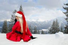 Bella donna bionda sexy che porta un vestito rosso e un cappello del ` s di Santa in montagne ed in neve Fotografia Stock