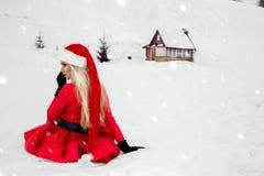 Bella donna bionda sexy che porta un vestito rosso e un cappello del ` s di Santa in montagne ed in neve Immagine Stock Libera da Diritti