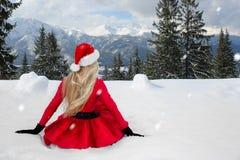 Bella donna bionda sexy che porta un vestito rosso e un cappello del ` s di Santa in montagne ed in neve Fotografia Stock Libera da Diritti