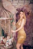 Bella donna bionda sexy che posa all'interno stare nel vestito dorato brillante e nel trucco luminoso immagini stock