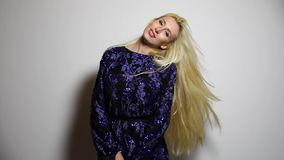 Bella donna bionda sexy nella posa lunga blu scuro del vestito contro il fondo dello studio Metraggio del movimento lento video d archivio