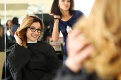 Bella donna bionda sorridente al parrucchiere Immagini Stock