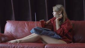 Bella donna bionda sorridente che si siede sullo strato facendo uso del suo computer portatile per acquisto online che tiene tazz stock footage