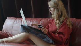 Bella donna bionda sorridente che si siede sullo strato facendo uso di Internet dei wi fi sul suo computer portatile per acquisto video d archivio