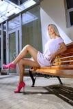 Bella donna bionda su un banco fotografia stock