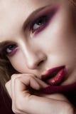 Bella donna bionda in un maglione rosso con trucco luminoso e le labbra scure Fronte di bellezza Ritratto del primo piano fotografia stock