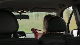 Bella donna bionda vestita in un'automobile La ragazza cambia i vestiti nella carrozza video d archivio