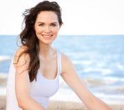 Bella donna in buona salute che si siede sulla spiaggia Fotografia Stock