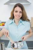 Bella donna calma che cucina sorridere alla macchina fotografica Immagine Stock