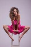 Bella donna, capelli ricci, sedentesi su un banco Immagini Stock