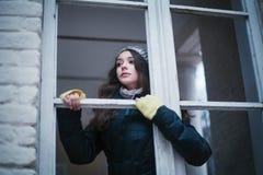 Bella donna in cappello che guarda attraverso la finestra Fotografia Stock