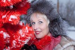Bella donna in cappello di pelliccia di inverno sull'albero di Natale rosso del fondo Fotografie Stock