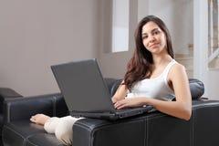 Bella donna a casa che scrive in un computer portatile Immagine Stock Libera da Diritti