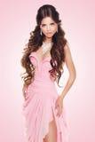Bella donna castana che dura in vestito di lusso sexy sopra il rosa Immagine Stock