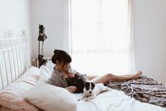 Bella donna castana che gioca con il cucciolo mentre trovandosi sul letto alla camera da letto immagini stock libere da diritti