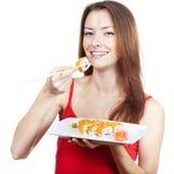 Bella donna castana che mangia i sushi Immagini Stock Libere da Diritti