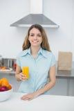 Bella donna castana che posa stare nella cucina che tiene un vetro di succo d'arancia Immagine Stock