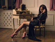 Bella donna castana che si siede su una retro sedia in vestito nero fotografia stock