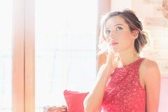 Bella donna castana che si siede vicino ad una finestra soleggiata Immagine Stock