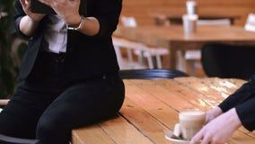 Bella donna castana di affari che lavora con una compressa mentre sedendosi alla tavola di legno video d archivio