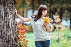 Bella donna castana elegante che cammina nel parco di autunno Immagine Stock