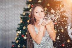 Bella donna castana nella neve di salto del vestito d'argento dal nuovo anno con le mani sul fondo dell'albero di Natale immagini stock