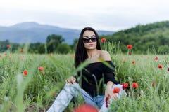 Bella donna castana in occhiali da sole e vestiti alla moda che si siedono fra sui papaveri rossi immagini stock libere da diritti