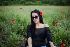 Bella donna castana in occhiali da sole e vestiti alla moda che si siedono fra sui papaveri rossi fotografie stock