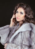 Bella donna castana in pelliccia del visone isolata sulla parte posteriore del nero Fotografia Stock