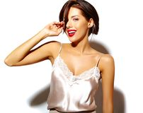 Bella donna castana sexy sveglia felice con le labbra rosse in biancheria dei pigiami su fondo bianco Fotografia Stock Libera da Diritti