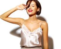Bella donna castana sexy sveglia felice con le labbra rosse in biancheria dei pigiami su fondo bianco Fotografia Stock